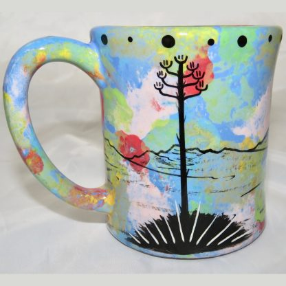 Ear handle mug, howling coyote, blue background. This is the reverse side showing Aravaipa vegetation.