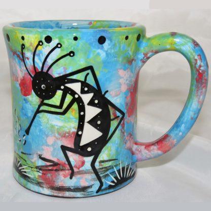 Ear handle mug, kokopelli, turquoise blue background.