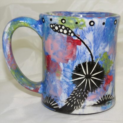 Ear-shaped handle mug with coyote on blue. Image shows reverse side.