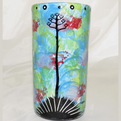 Mana Pottery tall clay tumbler with grey hawk on turquoise blue background. Phot shows reverse side with native Aravaipa vegetation.