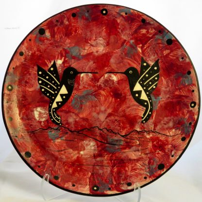 Mana Pottery 10-inch plate with kissing hummingbirds on crimson.