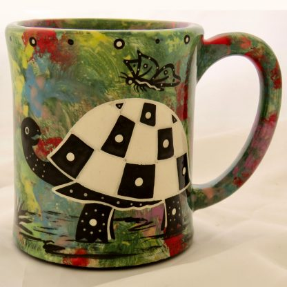 Mana Pottery emug featuring turtle with butterfly on one side and desert vegetation on reverse, on green