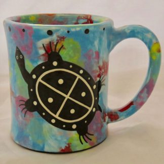 Mana Pottery emug featuring turtle on one side and desert vegetation on reverse, on turquoise blue
