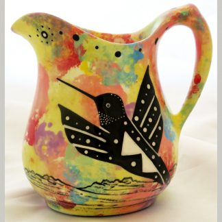 Mana Pottery cream pitcher featuring hummingbird on one side and native Aravaipa desert vegetation on reverse, on bright yellow background.