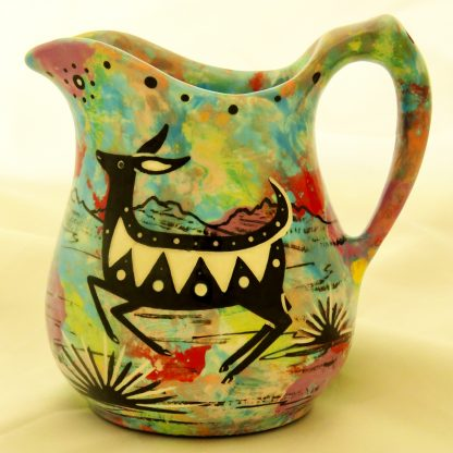 Mana Pottery cream pitcher featuring jumping deer on one side and native Aravaipa desert vegetation on reverse, on turquoise blue background.
