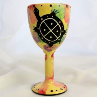 Mana Pottery goblet featuring turtle on one side and native Aravaipa desert vegetation on reverse, on bright yellow background.