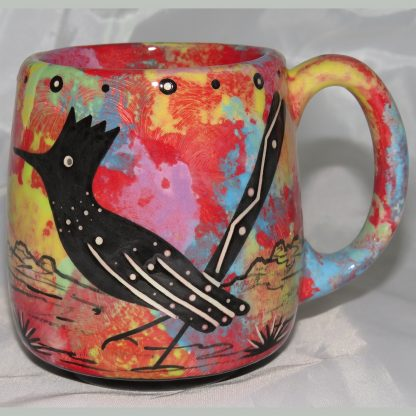 Mana Pottery Country Cup featuring road runner and desert vegetation on reverse sides, on crimson background.