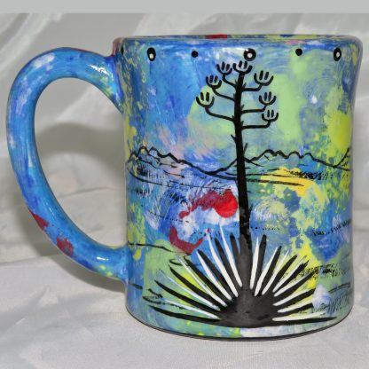 Mana Pottery e-mug featuring javelinas and desert landscape on reverse sides, on blue background.