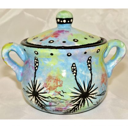 Mana Pottery honey pot with roadrunner in desert landscape on a background of turquoise blue.